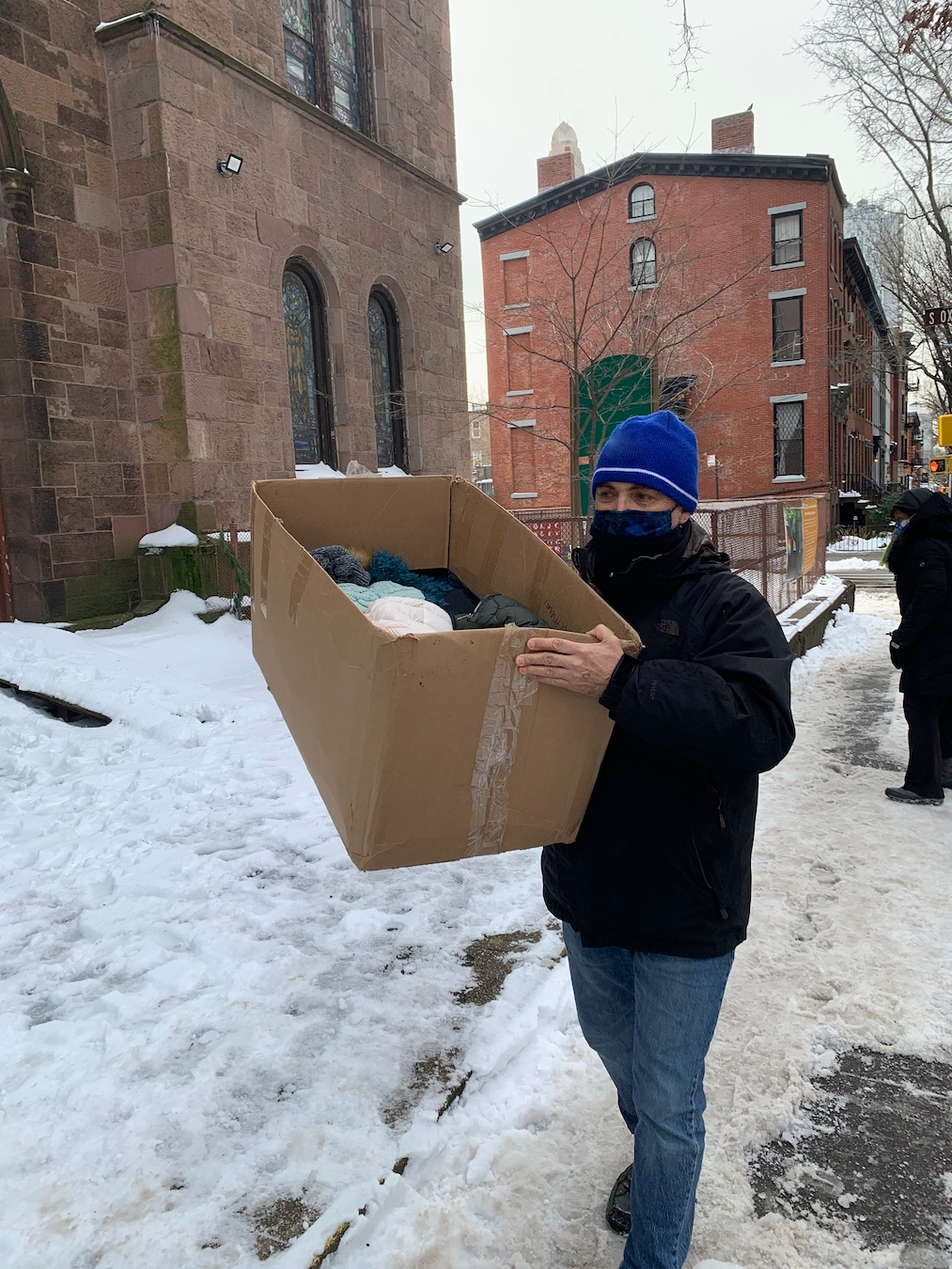 Man on the sidewalk carrying box of donated coats during 2020 drive.